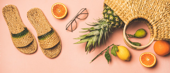 Summer apparel items. Flat-lay of summer flip flops, sunglasses, wicker bag and fresh fruits over pastel pink background, top view. Summer beach vacation concept
