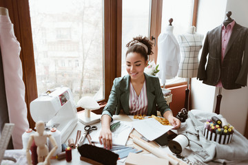 Wall Mural - Design studio. Young woman tailor with sewing machine is modeling new clothes
