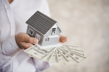 mortgage, investment, real estate and property concept - close up of home model on dollar money