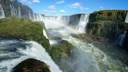 Iguazu Falls and rainbow on the Iguacu River. Located between Argentina and Brazil. Largest waterfalls system in the world.