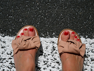 top view photo of woman feet in sandals on the pedestrian crossing
