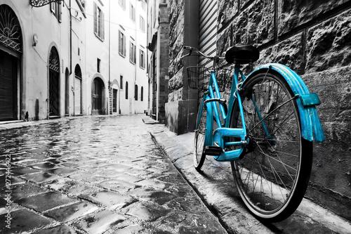 Fototapete Retro blue bike on old town street.