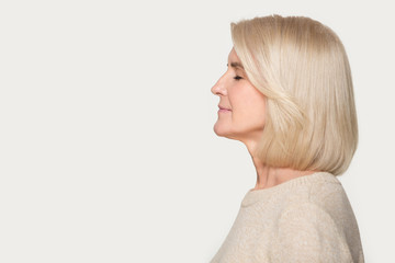 Profile view aged woman standing aside on grey studio background