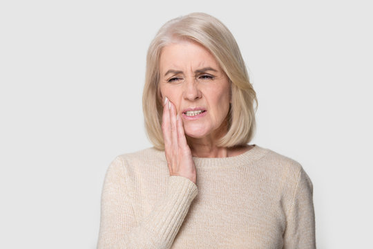 Headshot portrait mature woman touches cheek suffers from tooth ache