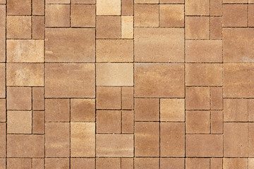 The surface is paved with road tiles of different sizes (multiformat). The uneven (melange) color of the tile makes it look like a natural stone. View from above.
