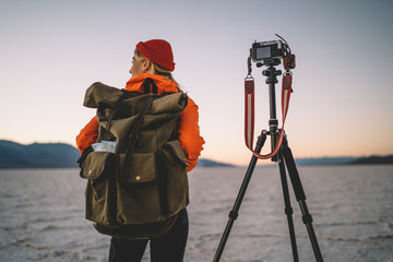 Back view of female photographer with backpack making preparation before starting to shoot video of scenic environment, woman taking photos of Badwater basin using modern equipment and tripod