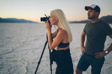 Young woman taking picture of wild environment of dry lake traveling with boyfriend in Badwater basin, journalists colleagues shooting video together using camera and tripod during expedition