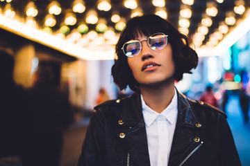 Half length portrait of gorgeous brunette young woman in stylish eyeglasses looking at camera.Charming caucasian hipster girl with short haircut dressed in fashionable wear standing in night New York Wall mural