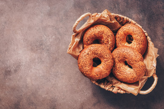 Fresh homemade bagels with sesame seeds in a basket on a dark background. Top view, flat lay, copy space.