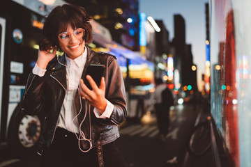 Cheerful pretty young woman in cool eyeglasses and trendy wear walking on metropolis street with night lights enjoying songs from playlist in earphones and reading sms with good news on smartphone