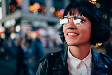Charming positive brunette young woman in cool spectacles enjoying night street standing on bokeh background.Cheerful attractive hipster girl in stylish eyeglasses and leather jacket laughing Wall mural