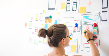 A young female designer is developing a web application for mobile phones. Woman draws a mockup of interface to smartphone. User experience.