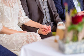 Wedding Scenery: Couple is attending the wedding ceremony while holding their hands - symbol of marriage and wedding.