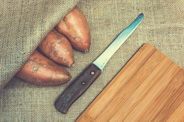 Raw sweet potatoes on a wooden cutting board and jute backgroud. Product photo of batats. Healthy diet for vegetarians and vegans. Source of vitamins. Wooden plank with batatas and knife