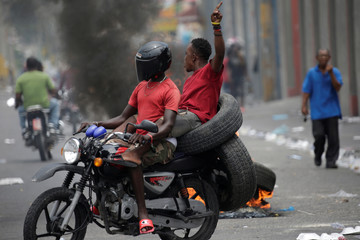 Two men ride a motorbike carrying tires as they pass next to a burning tire during a strike in Port-au-Prince