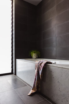 Luxury black bathroom with marble bath and full height tiling
