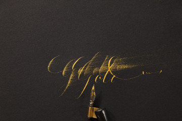 """the word """"""""Gold"""""""" hand-written with golden ink and a nib mounted on a oblique holder"""