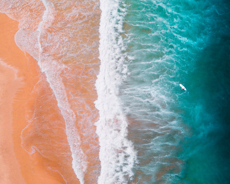 An aerial shot of the ocean shore and waves coming