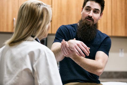 Clinic: Doctor Examines Man's Wrist Injury