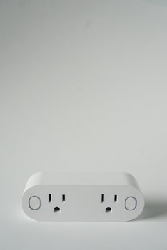 This double smart WIFI plug outlet can switch an electric device on or off via wi-fi. Isolated on a vertical white background with copyspace or empty room space for text or copy.