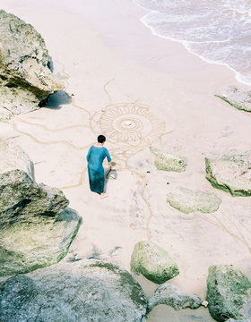 Asian woman drawing a mandala pattern on a beautiful rocky beach ,during a comfortable journey. shot by 120 films