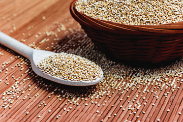 White seeds of Quinoa in a wooden spoon and a wicker bowl. Healthy nutrition and superfoods. Latin name Chenopodium quinoa. Food for gluten-free diet. Food for vegetarians and vegans.