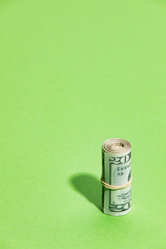 Wealth: Money Roll Of Twenty Dollar Bills On Green Background