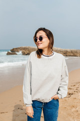 Young woman on the shore of the beach with sunglasses
