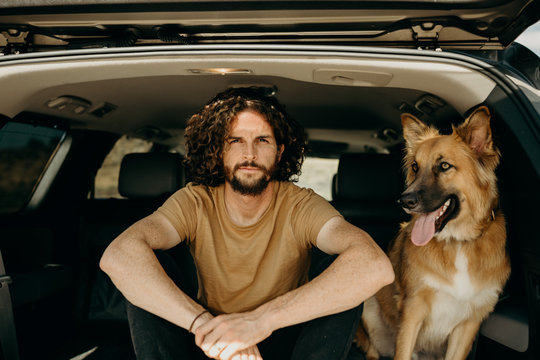 guy sitting in car with dog