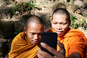 Two monks with cell phone.