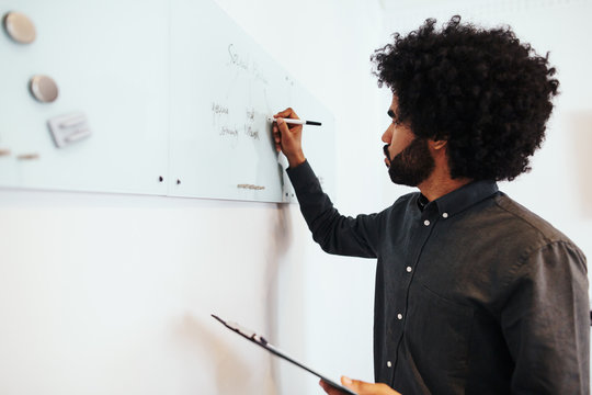 Afro businessman writing on white board.