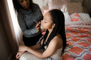 black teen girl getting her make up done for prom
