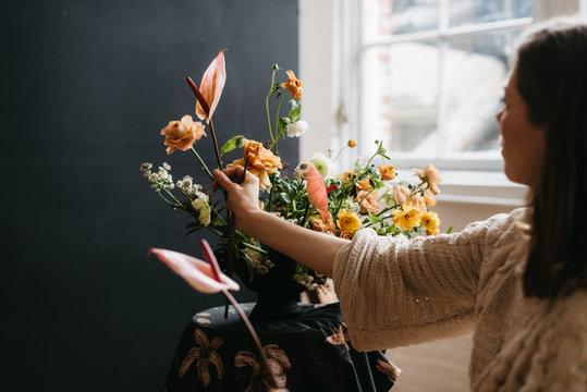 Florist in studio building a stunning floral arrangement