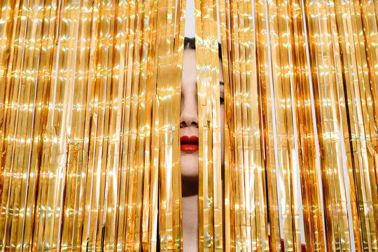 Woman hiding behind thread curtain