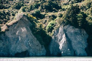Glacial water runs alongside steep white cliff.