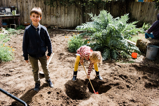 little girl and her friend digging and planting apple seeds