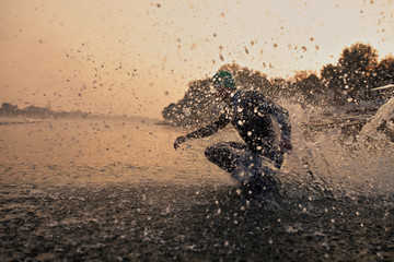 Triathlete running into water.