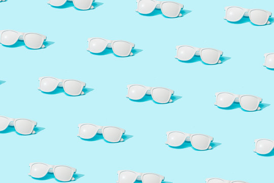 Trendy sunlight Summer pattern made with white painted sunglasses on bright light blue background. Minimal summer concept.