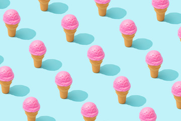 Trendy sunlight Summer pattern made with pink strawberry ice cream on bright light blue background. Minimal summer concept.