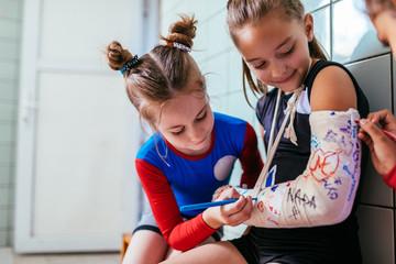 Girls sign plaster cast on a broken arm