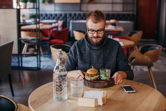 Stylish man eating burger at restaurant