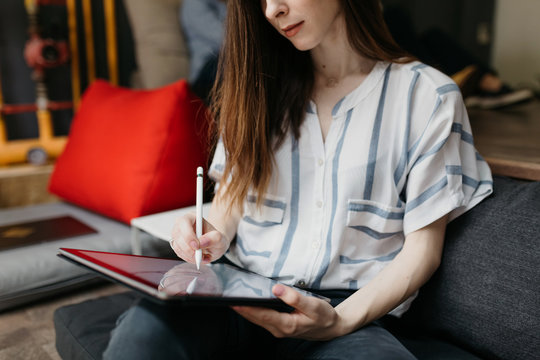 Brunette woman drawing on a tablet in the offce