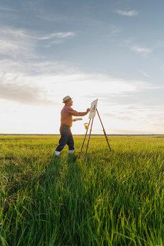 Senior man painting in field