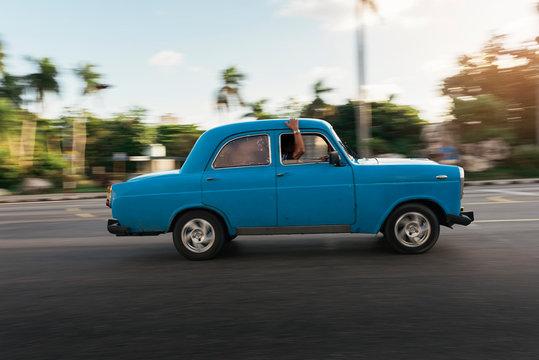 Vintage blue shiny car riding on road