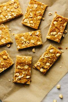 Close up of hazelnut granola bars on baking parchment overhead