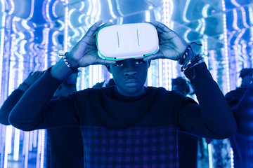 Casual black man in VR goggles in neon