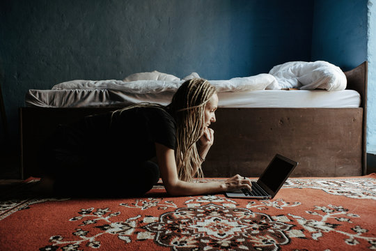 Young woman using laptop in bedroom