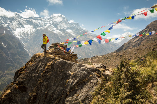 Female Hiker on Outcropping with Prayer Flags