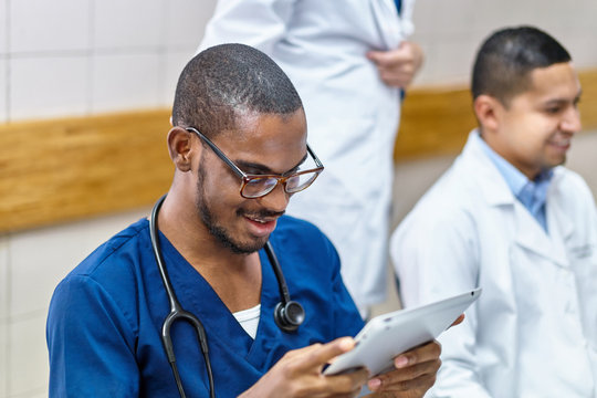 Smiling doctor with tablet doing administration on a tablet