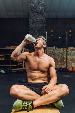 Tired man drinking water in gym